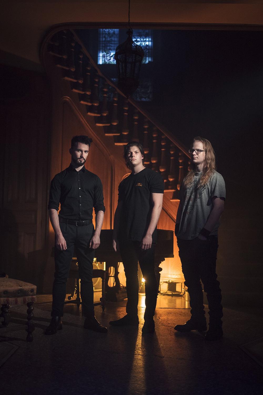 photo de 3 hommes devant un escalier avec une lumière tamisée