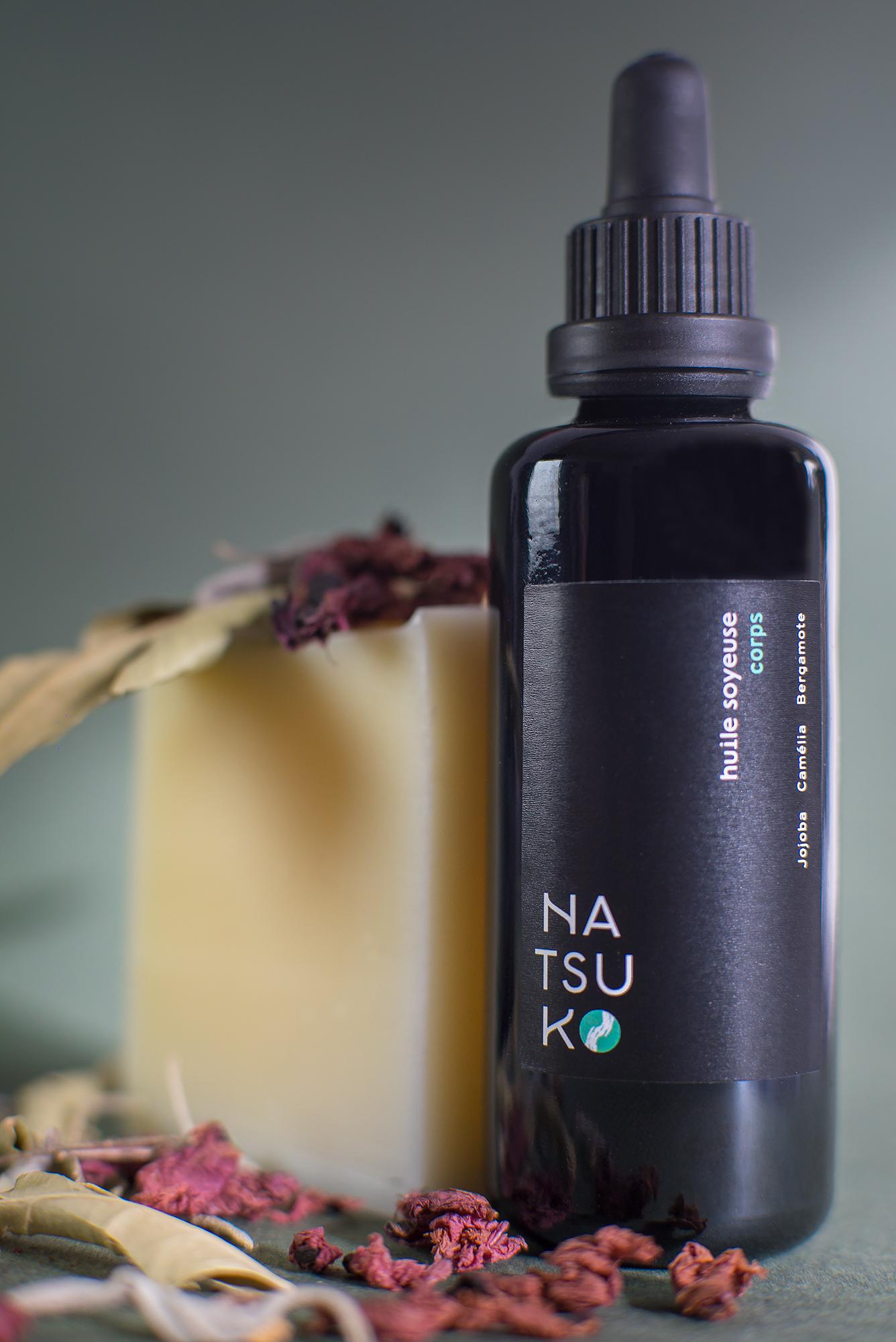 photo d'un flacon d'huiles essentielles et d'un savon dans un décors fleuri