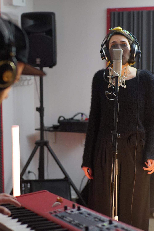 photographie d'une fille chantant dans un micro en studio avec un clavier électronique